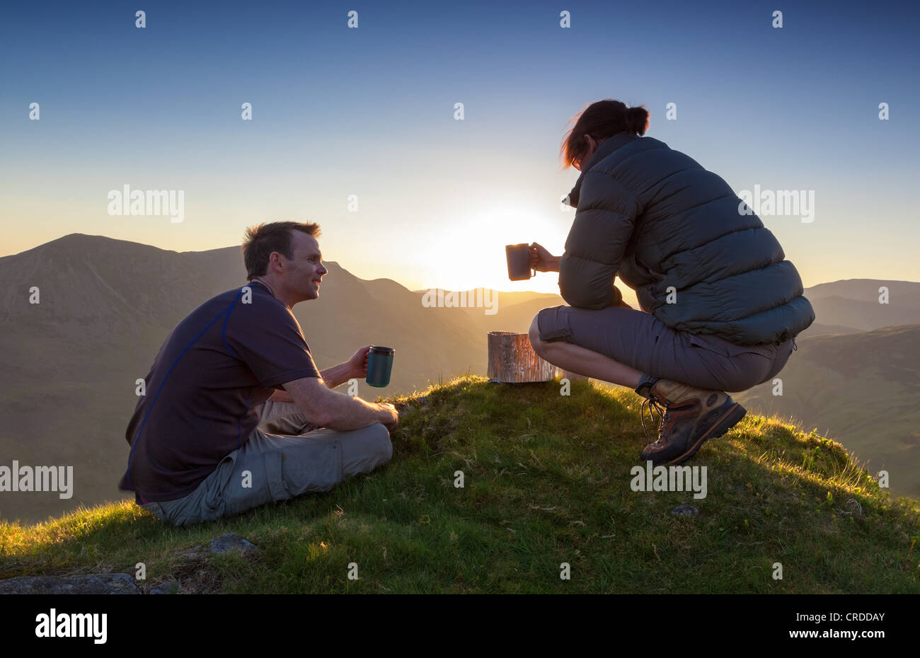 A couple enjoy a chat and a hot drink as the sun sets over Lake Buttermere in the Lake District. - Stock Image