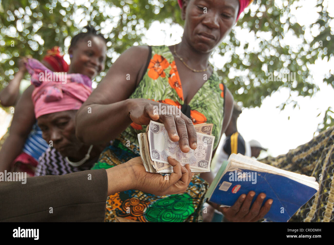 A woman receives money during a social cash transfer programme distribution in the village of Julijuah, Bomi county, - Stock Image