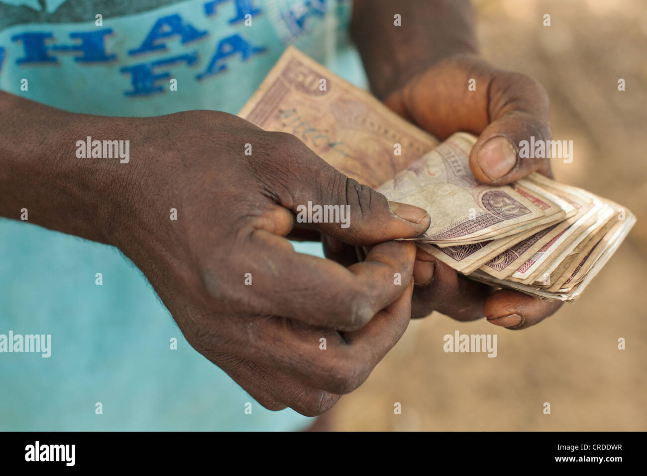 A man counts money he's just received from a social cash transfer programme in the village of Julijuah, Bomi - Stock Image