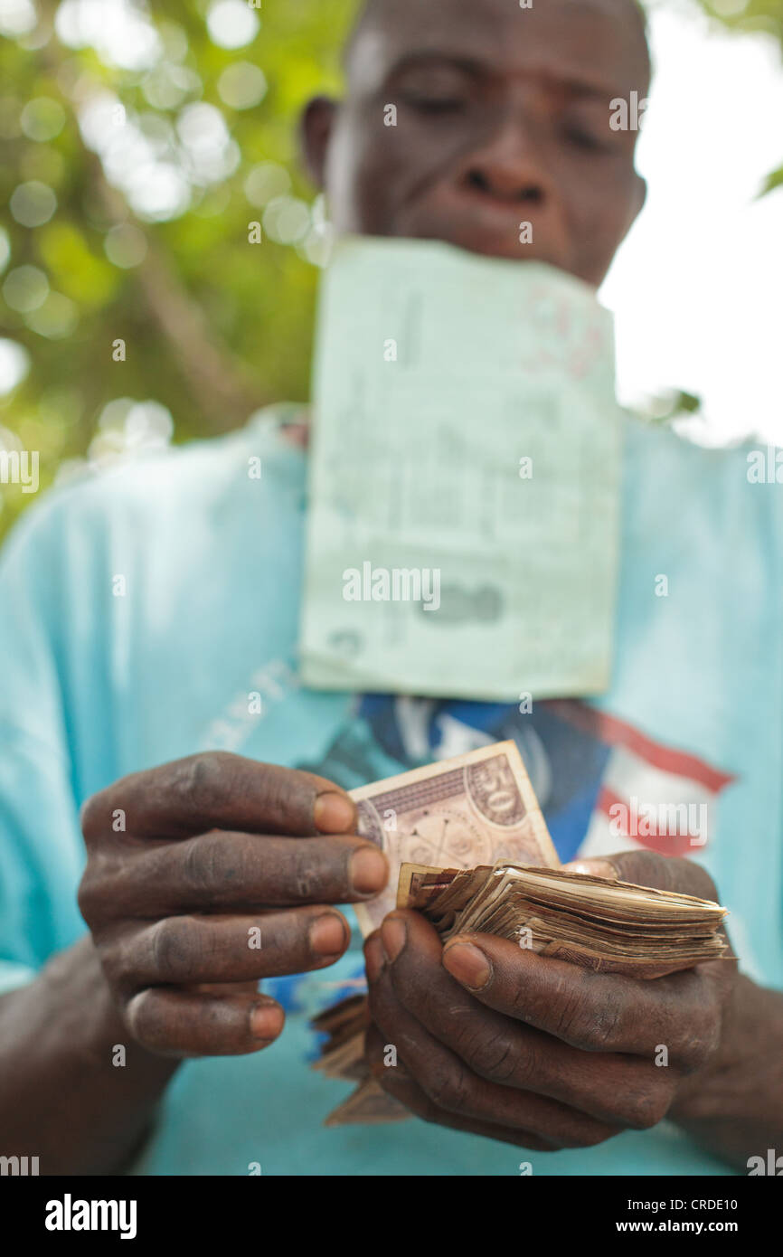 A man counts money he's just received from a social cash transfer programme in the village of Julijuah, Liberia - Stock Image