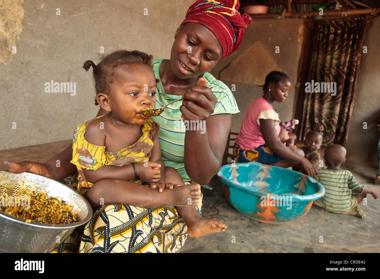 Jenneh Johnson, 31, feeds her daughter Jusu, 2, at home in the village of Julijuah, Bomi county, Liberia - Stock Image