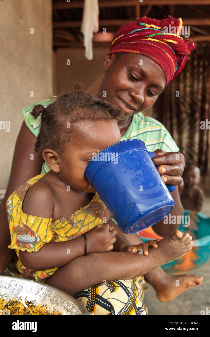 Jenneh Johnson, 31, gives water to drink to her daughter Jusu, 2, at home in the village of Julijuah, Bomi county, - Stock Image