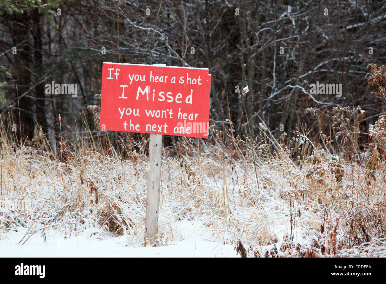 """Property sign with a sense of humor (or maybe not); rural Minnesota.  """"If you hear a shot I Missed you won't hear Stock Photo"""