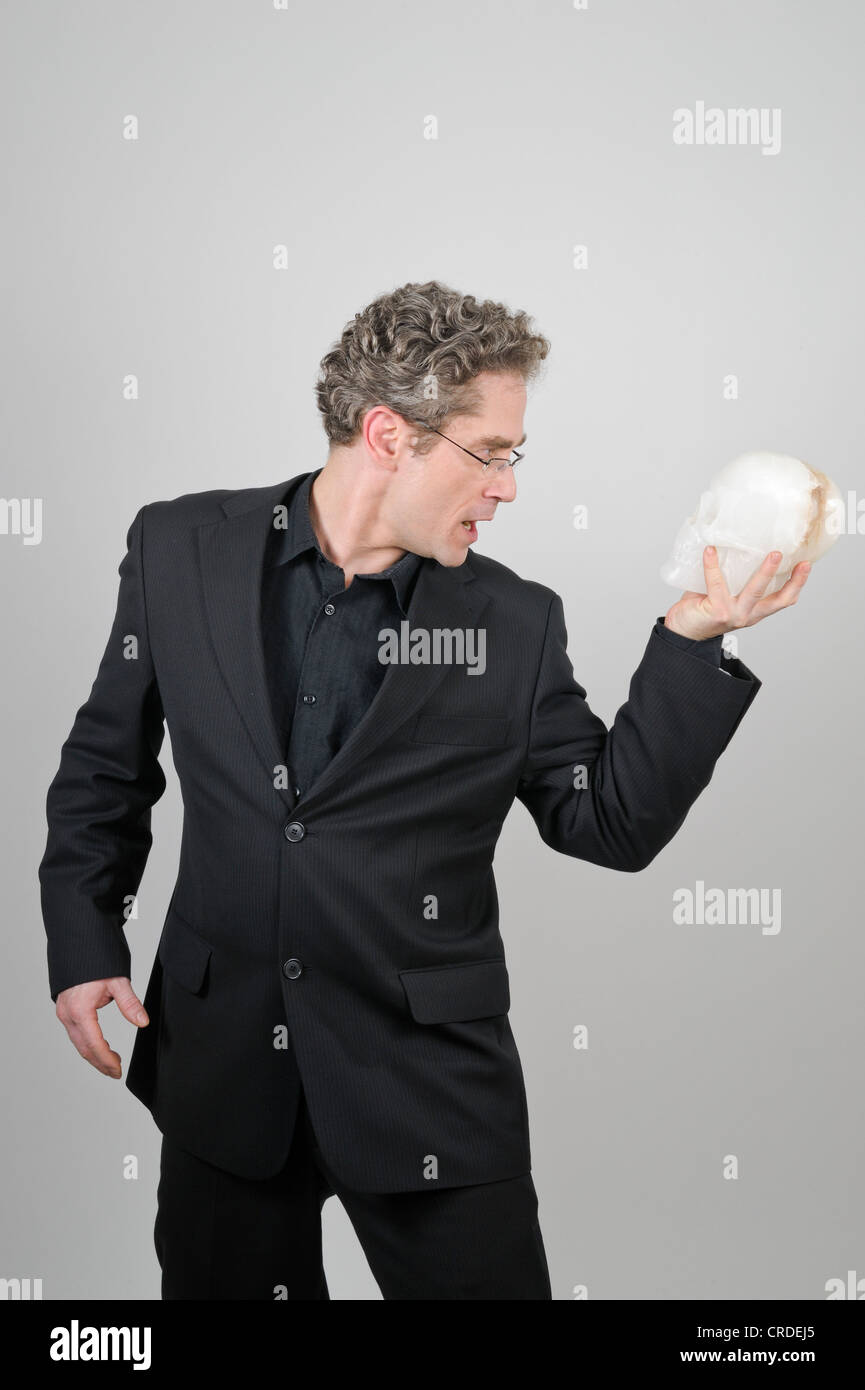 Businessman wearing a black suit holding a white skull made of alabaster in his hand, To Be or Not to Be, Shakespeare's - Stock Image