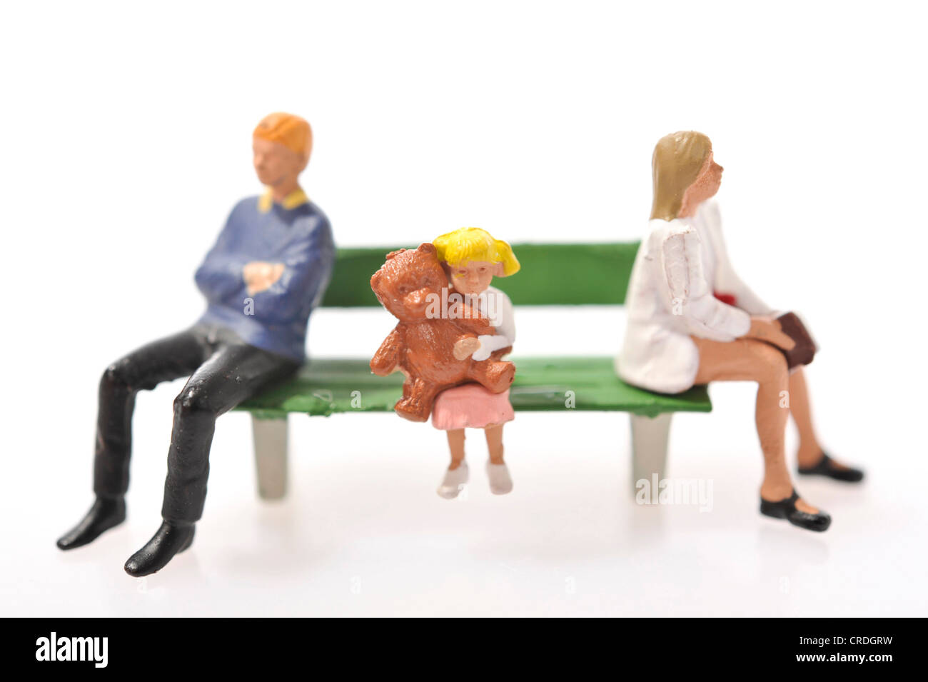 Figurines, family sitting on a bench - Stock Image