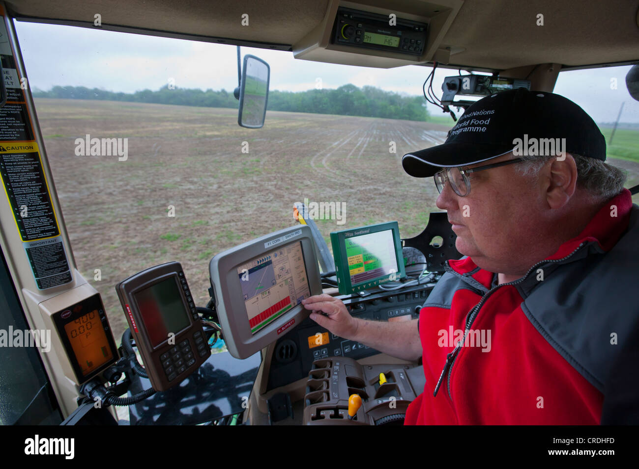 Farmer Inside Combine Cab Using Gps And Other Technology