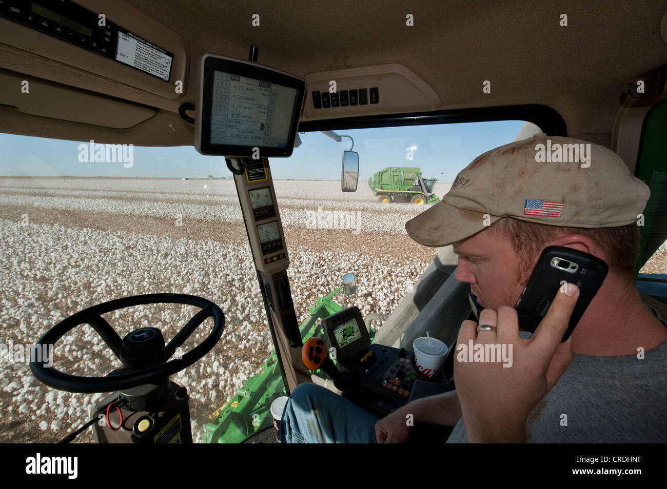 Inside Of A Combine : Farmer inside combine cab on cell phone while using gps