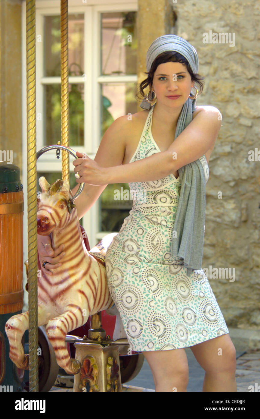 young women sitting on a merry-go-round horse, Germany - Stock Image