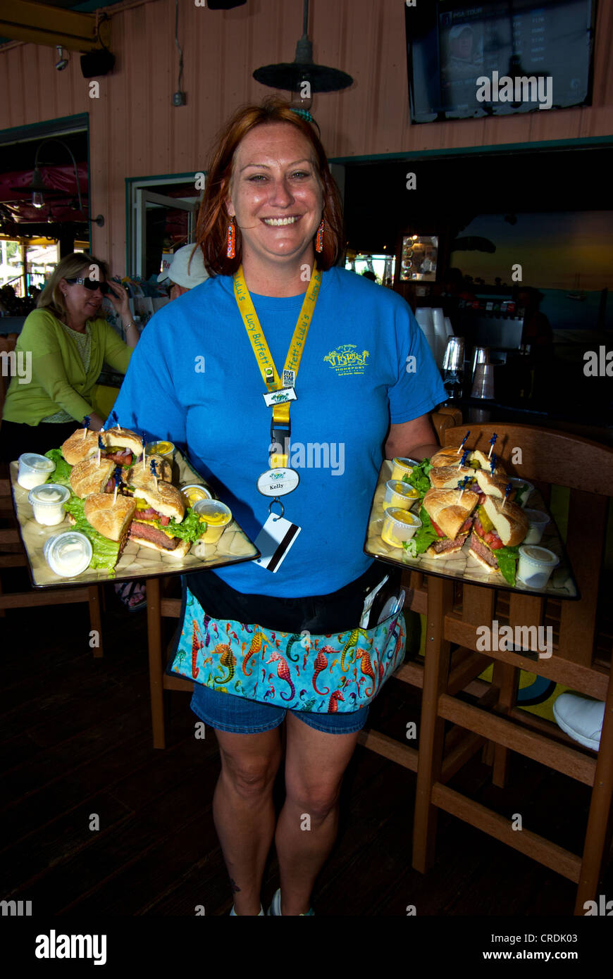 Waitress Lulu's Restaurant Homeport Marina two platters deluxe hamburgers - Stock Image