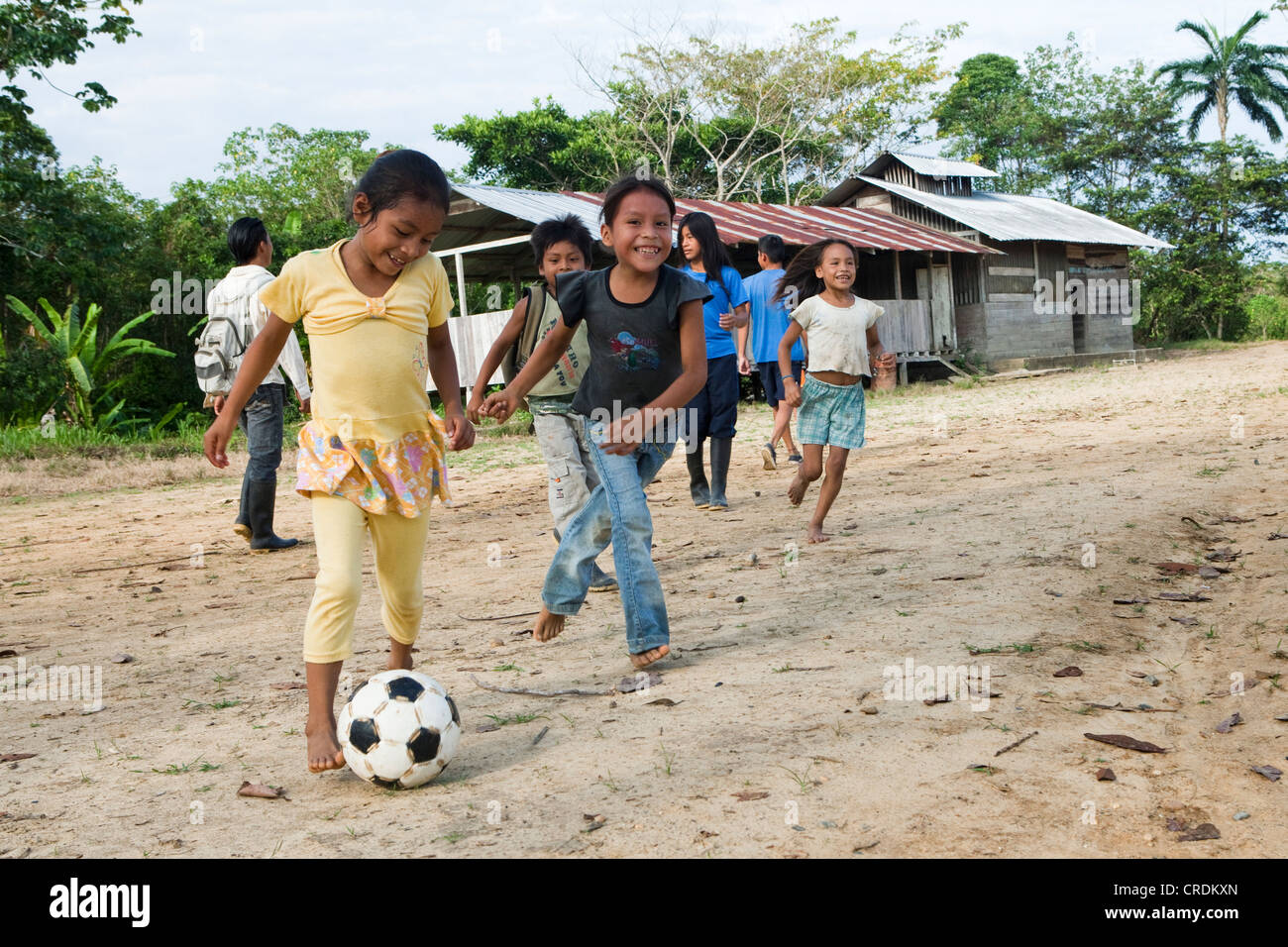 School children playing soccer in the schoolyard before classes start in a village with no road access in the rainforest - Stock Image