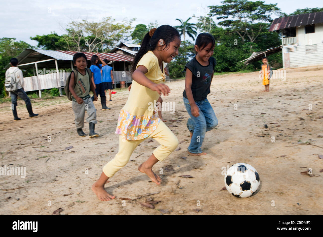 School children playing football in the schoolyard before the start of the lessons, in a village without road access - Stock Image