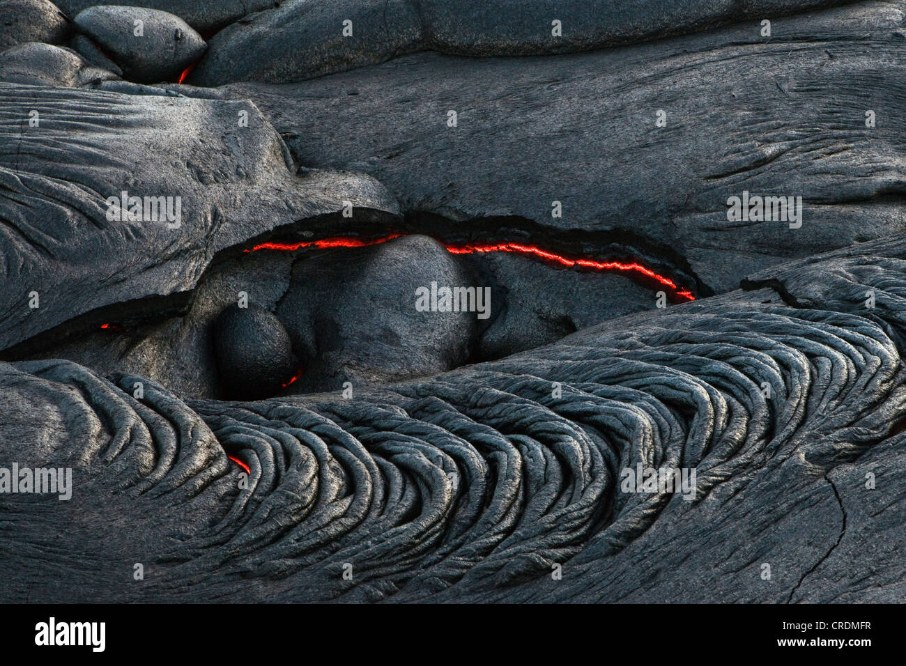 Viscous Pāhoehoe lava flowing from rifts in the East Rift Zone towards the sea, lava field at the Kilauea - Stock Image