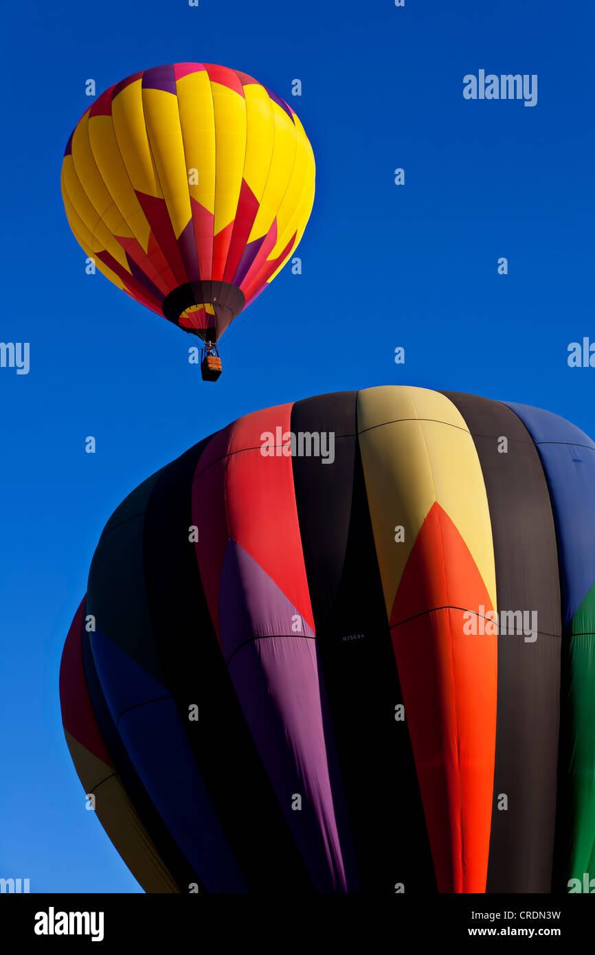 Hot air balloon rising into clear blue sky. Stock Photo