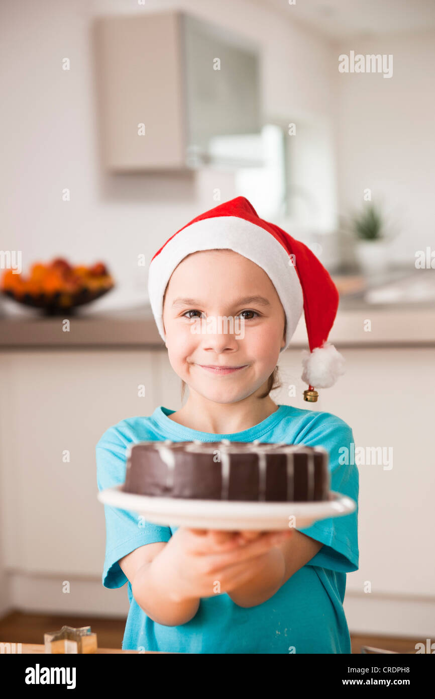Girl with Santa Claus hat presenting a chocolate cake - Stock Image