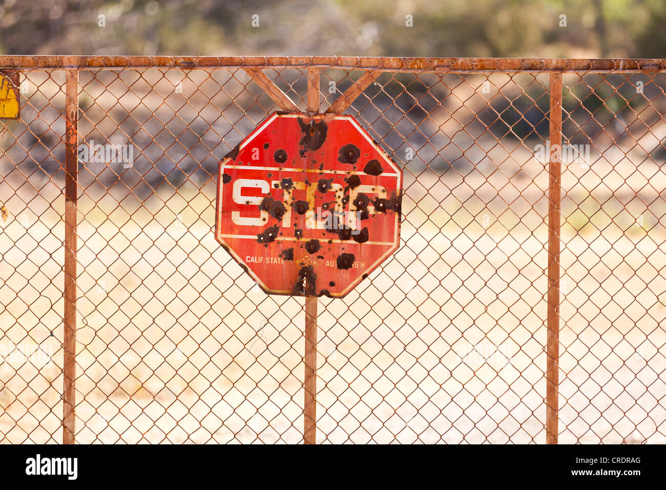 Rusty stop sign with bullet holes Stock Photo