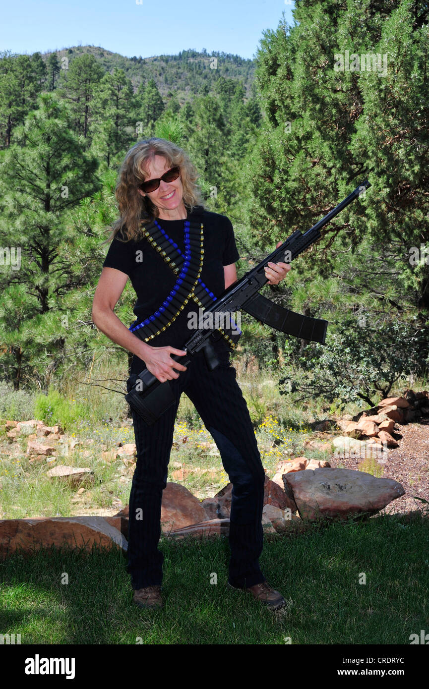 A Blonde Woman Standing in the Forest Holding a Shotgun and Bandolier Belt of Ammo - Stock Image