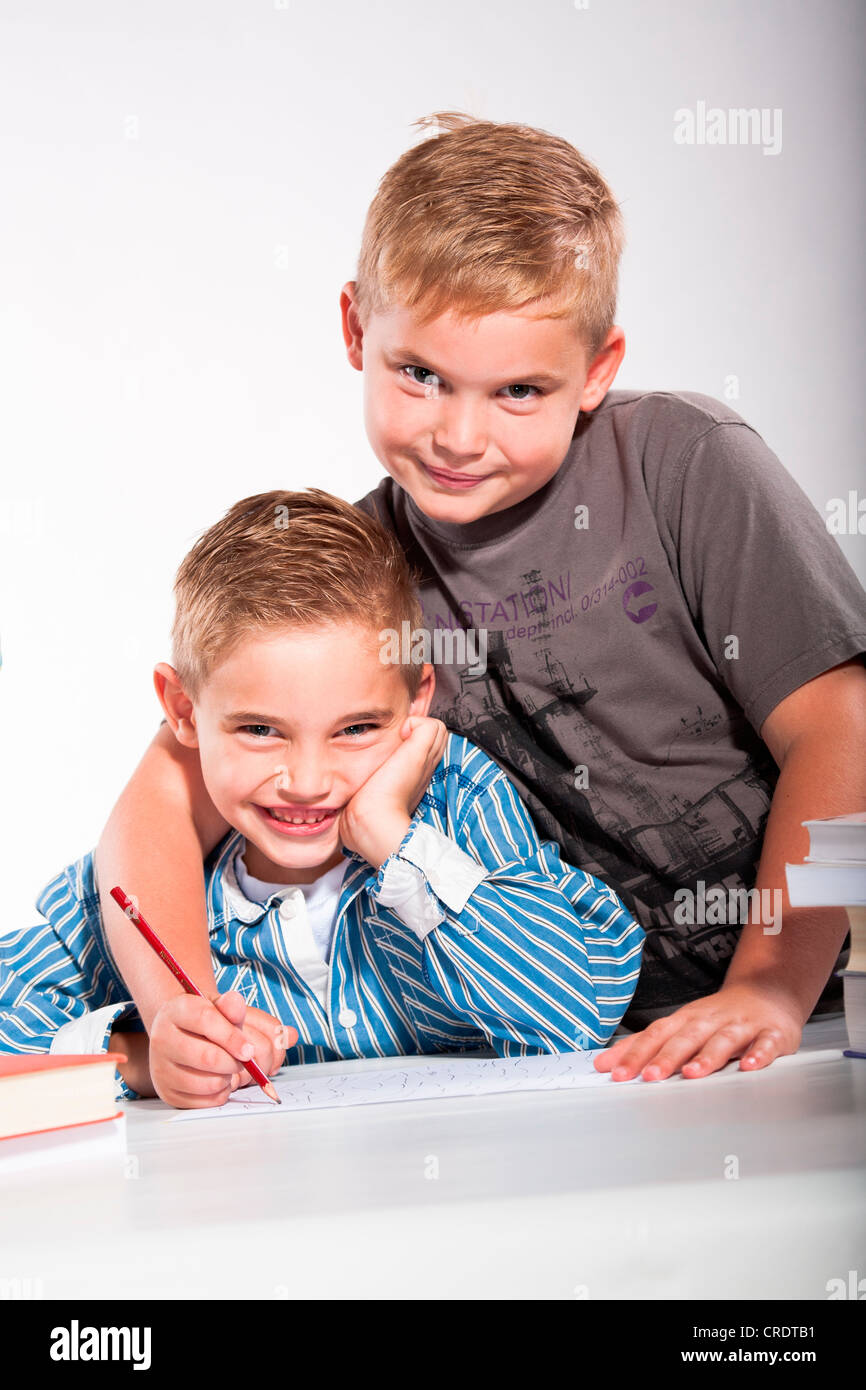 Boy helping his younger brother with his homework - Stock Image