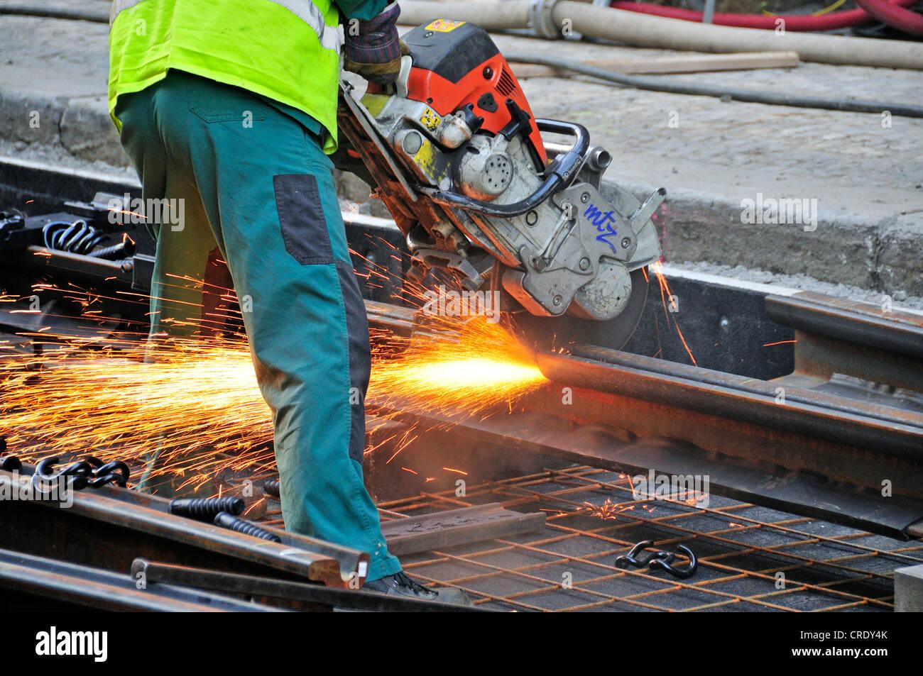 Worker with angle grinder cutting tram rails, Prague, Czech Republic, Europe, OeffentlicherGrund - Stock Image