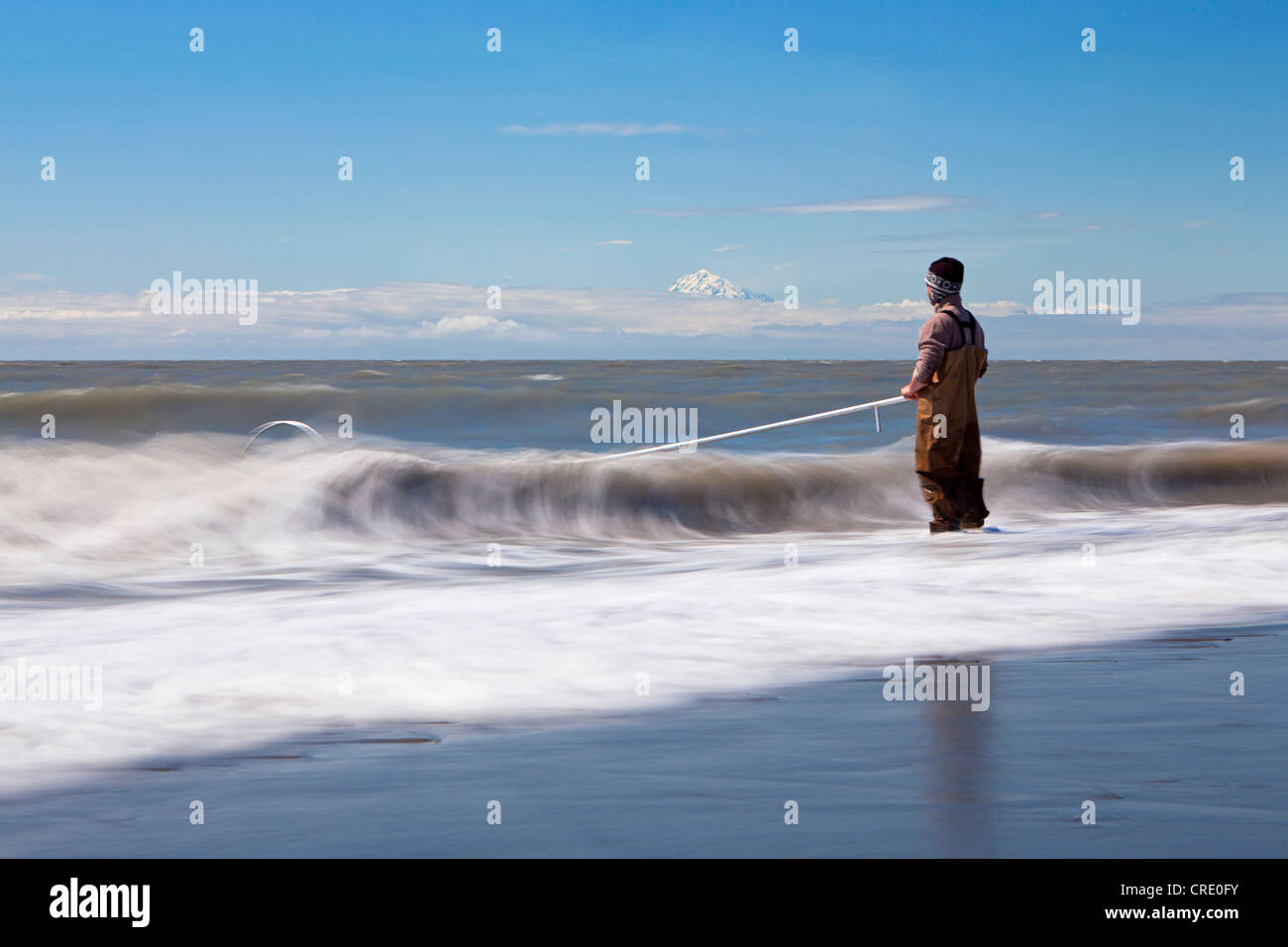 Surf zone with a fisherman on the beach in Kenai on the Kenai Peninsula with Mount Redoubt volcano in the Cook Inlet, - Stock Image