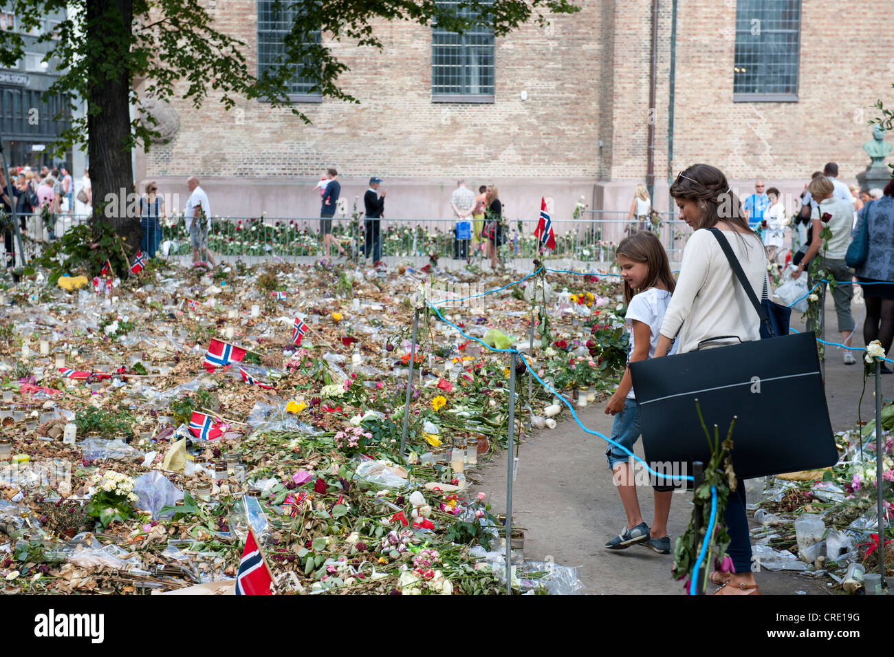 Flowers and flags to commemorate the victims of the attacks from 22 July 2011 at Oslo Cathedral, Oslo Domkirke, - Stock Image