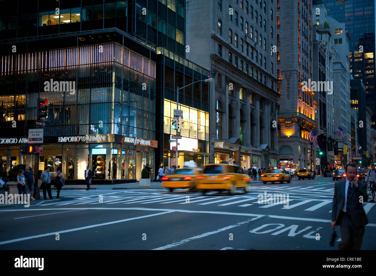 Traffic at dusk, yellow cabs, taxis, Armani store at back, 5th Avenue, Midtown, Manhattan, New York City, USA, North - Stock Image