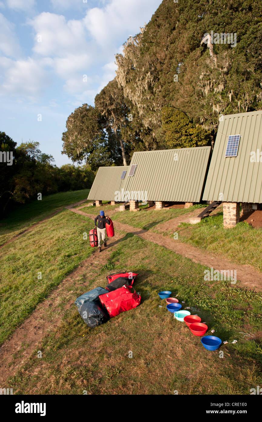 Mountaineering, trekking, carrier with luggage outside mountain huts, plastic bowls for washing, Mandara Hut, Marangu - Stock Image