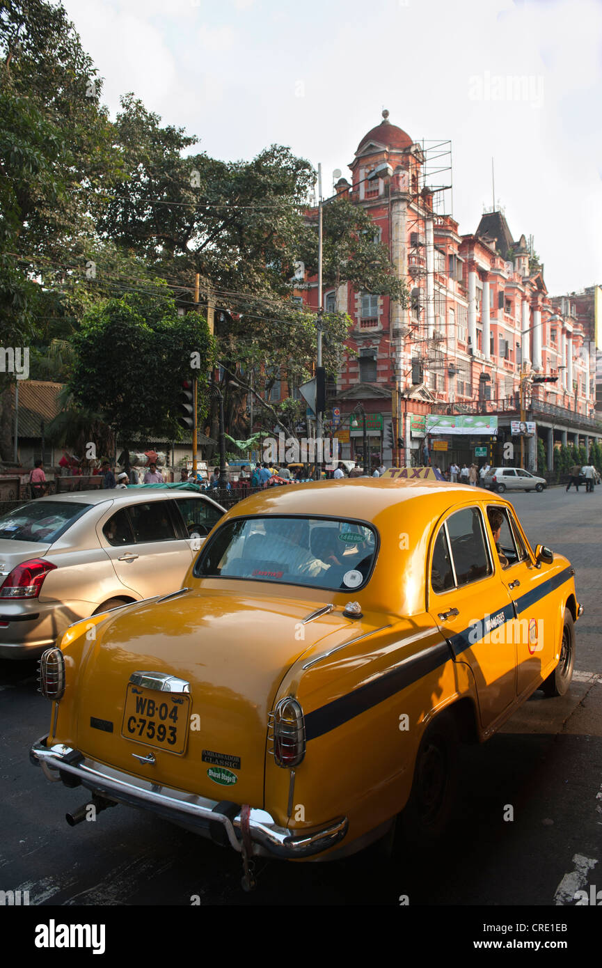 Transportation, yellow Ambassador taxi, old British colonial architecture, Chowringhee, Calcutta, Kolkata, West - Stock Image