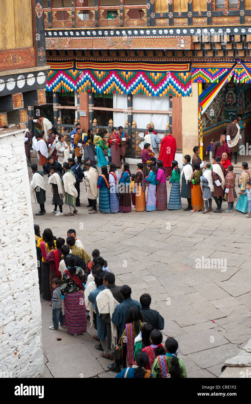 Tibetan Buddhist festival, people wearing the traditional Gho robe standing in a queue, Rinpung Dzong Monastery - Stock Image