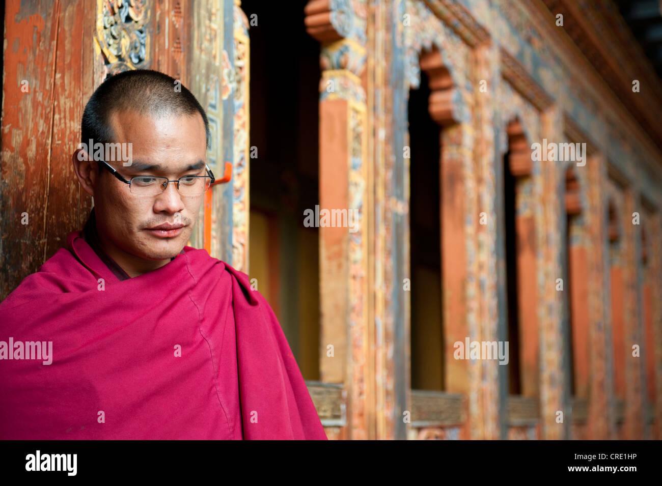 Tibetan Buddhism, monk in a red robe, ornate wooden wall, Tango Goemba Monastery, near Thimphu, the Himalayas, Kingdom - Stock Image