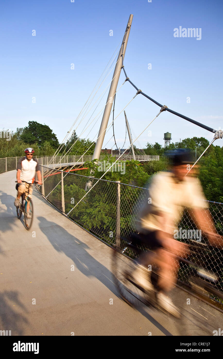 cyclists on the Erzbahn cycle way with the water tower of the Jahrhunderhalle in the background, Germany, North - Stock Image