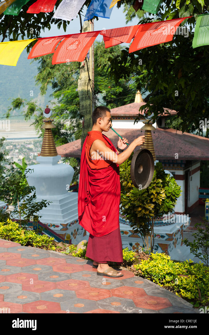 Tibetan Buddhism, monk in a red robe beating the gong, Kharbadi Gompa, Phuentsholing, Kingdom of Bhutan, South Asia, - Stock Image