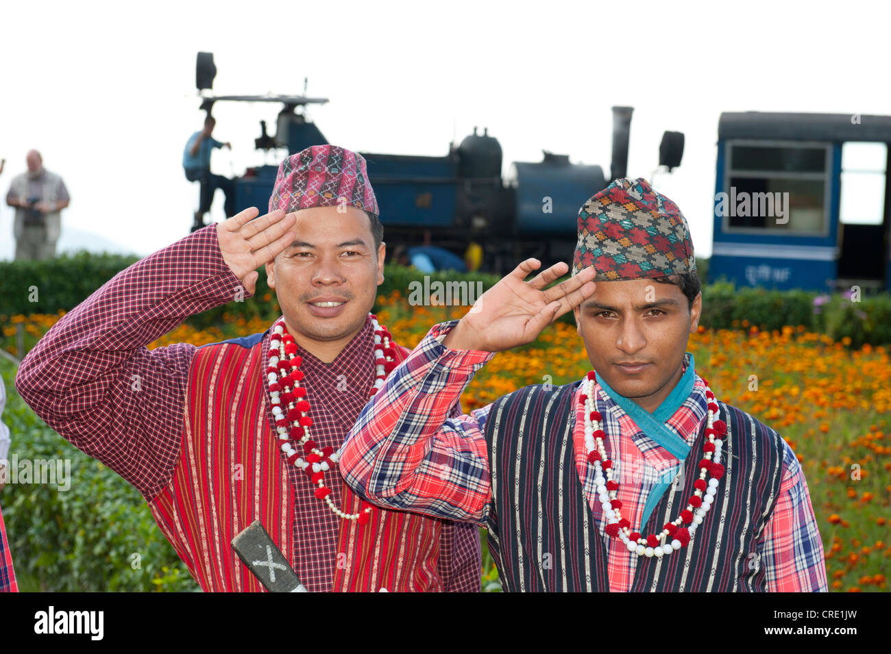 Two Nepali men in traditional costume saluting, historic train at back, Darjeeling Himalayan Railway, narrow-gauge - Stock Image