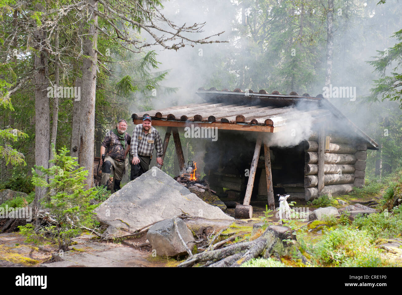 Swedish forestry workers and hunters making coffee on a fire in a cabin in the woods, near Fulufjaellets National - Stock Image