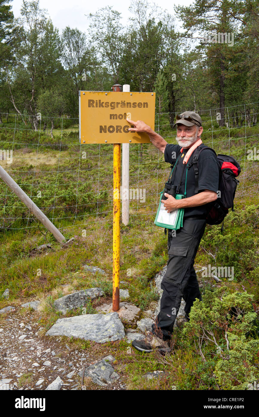 Hikers pointing to a sign on the border to Norway in a forest, Riksgraensen mot Norge, Valdalsbygget near Groevelsjoen - Stock Image