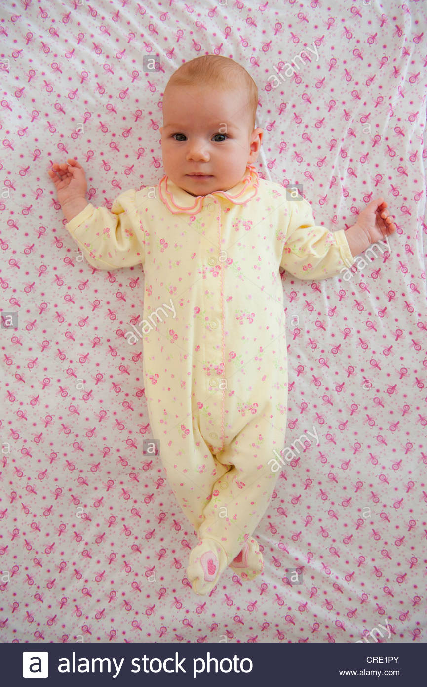Baby girl in a romper lying on a blanket with crossed legs - Stock Image