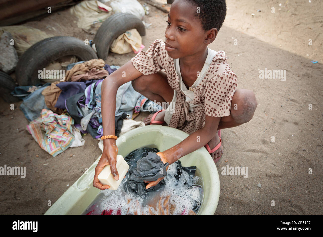 A girl hand washes clothes in the Point Four neighborhood of Monrovia, Montserrado county, Liberia on Thursday April - Stock Image