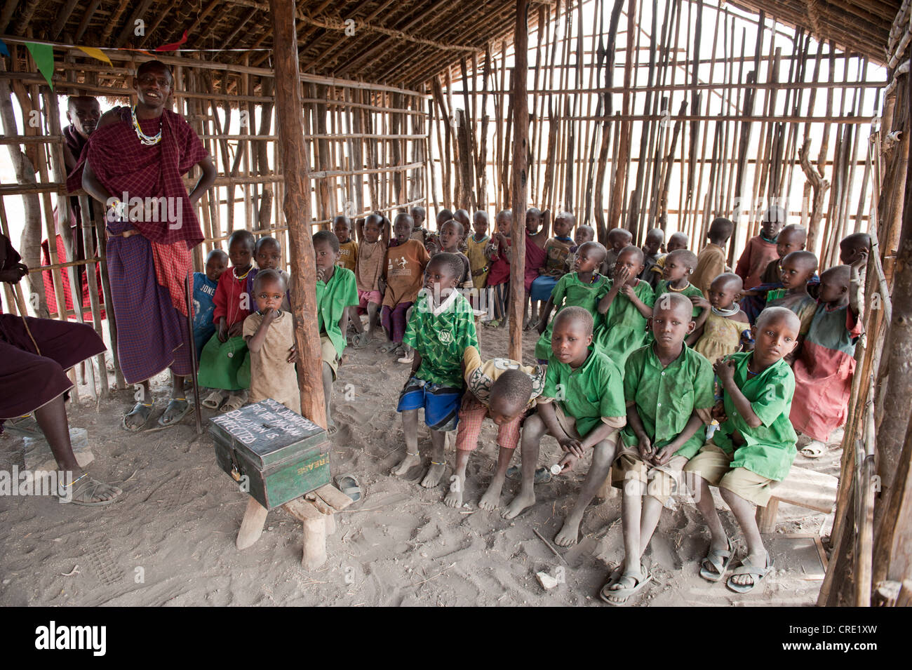 Education and poverty, children in a primary school class with a teacher, ethnology, Masai, village of Kiloki, Savannah - Stock Image