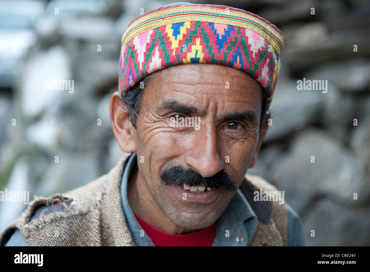 Portrait, Man wearing a typical brightly coloured decorated cap, Manali, Kullu district, the Himalayas, Himachal Stock Photo