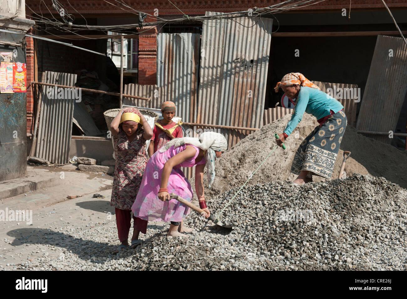 Hard physical labor, construction workers shoveling gravel with shovels, Durbar Square, Kathmandu, Kathmandu Valley, - Stock Image