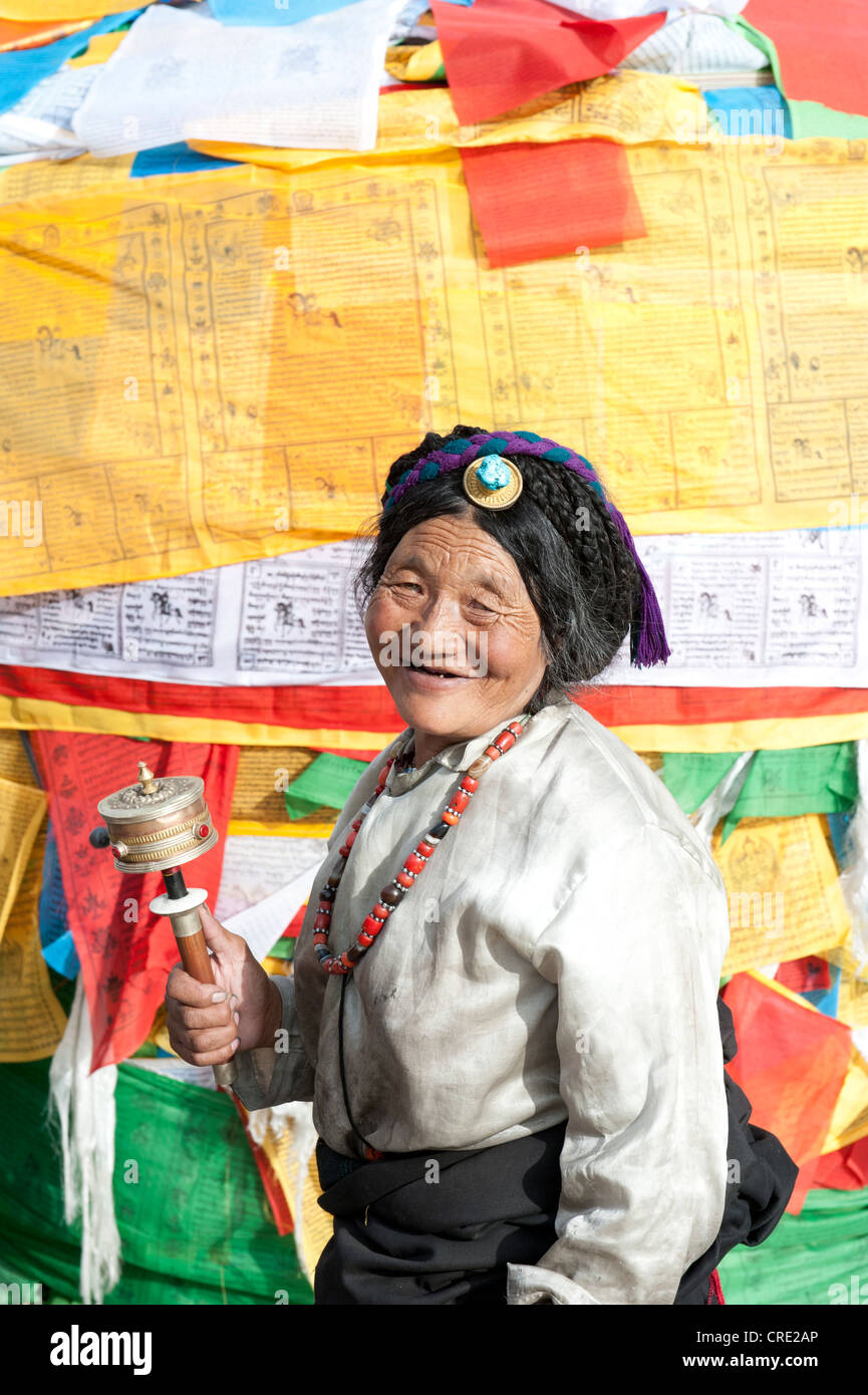 Tibetan Buddhism, devout Tibetan with prayer wheel in front of colorful prayer flags, Barkhor Square, Lhasa, Himalayas, - Stock Image