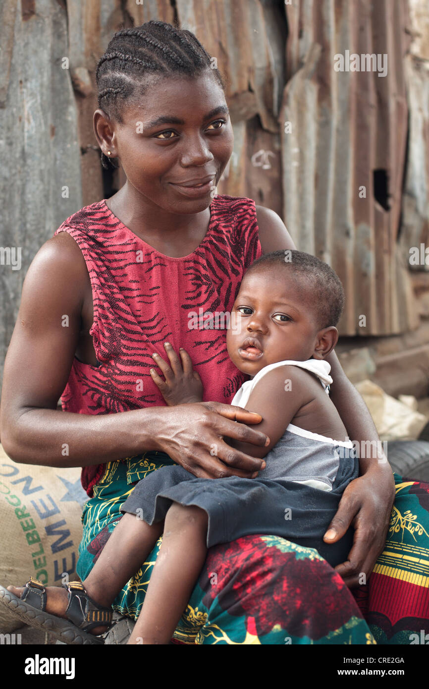 A young boy sits on his mother's lap in the Point Four neighborhood of Monrovia, Montserrado county, Liberia - Stock Image