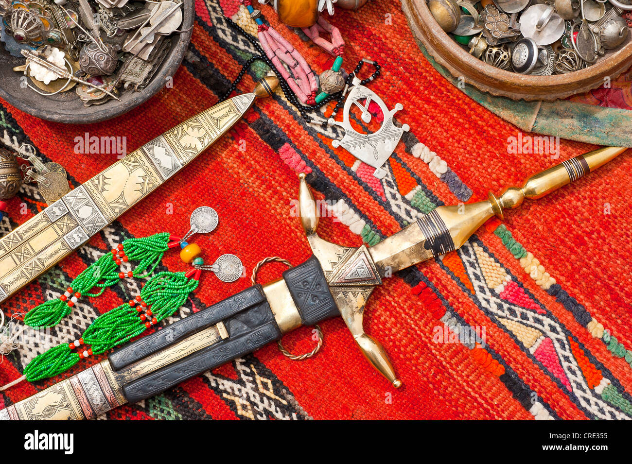 Oriental jewellery and ornate Touareg knives are spread on a carpet, souk, bazaar, Morocco, Africa - Stock Image