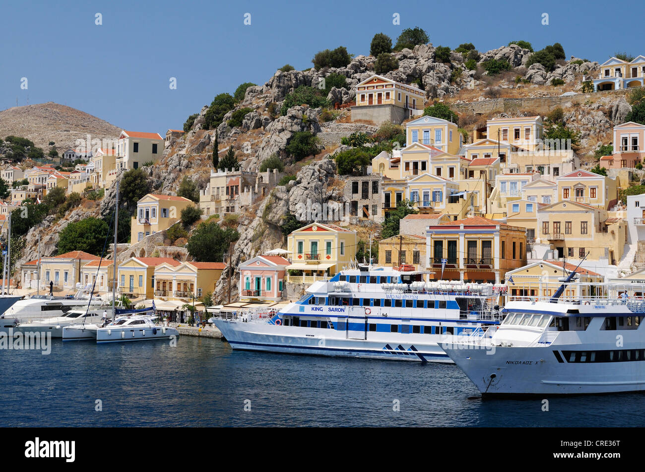 Dock with excursion boats at the center of the island of Symi near Rhodes, Greece, Europe - Stock Image