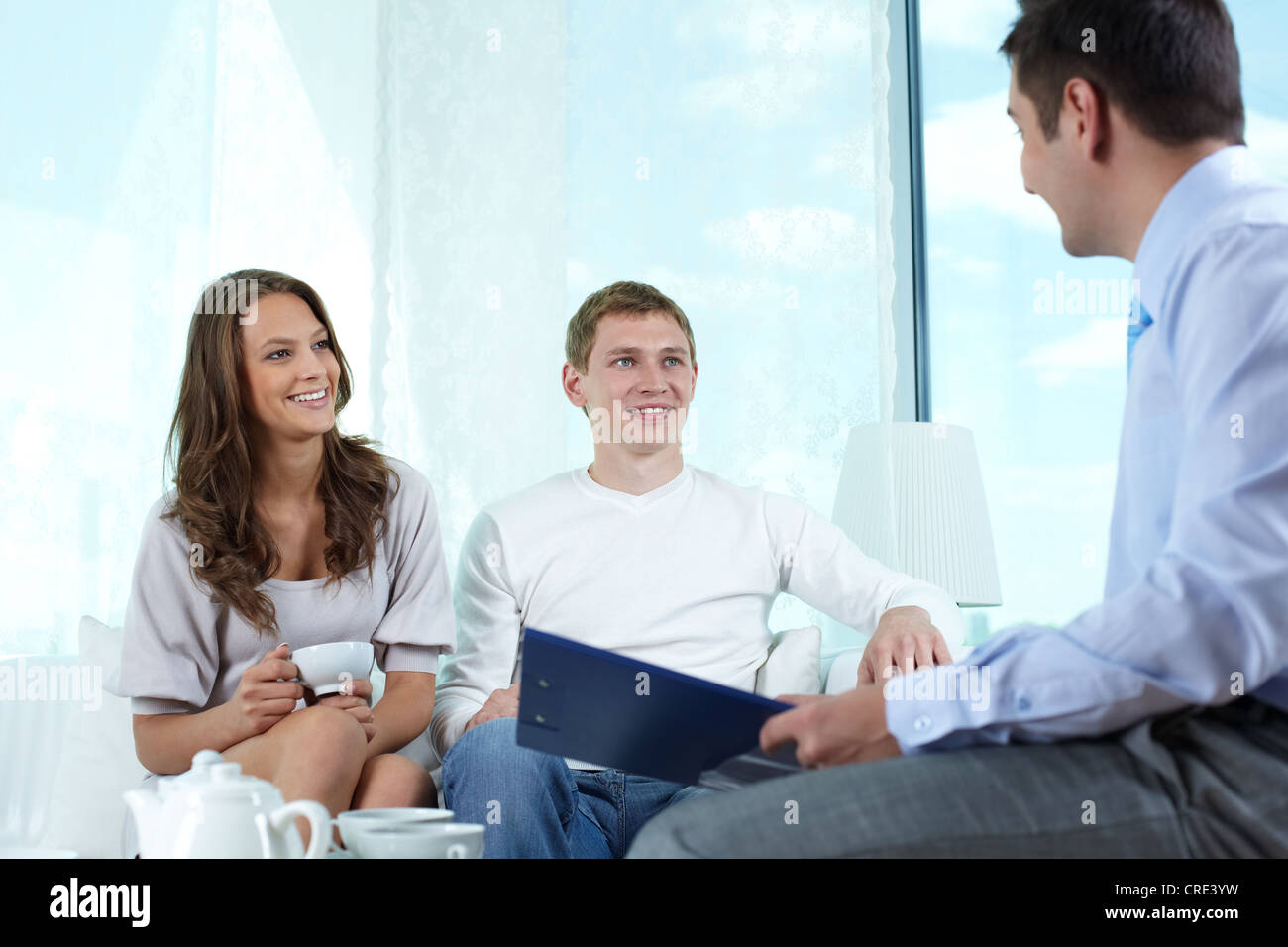 Smiling insurance agent making a business proposition to a lovely couple - Stock Image