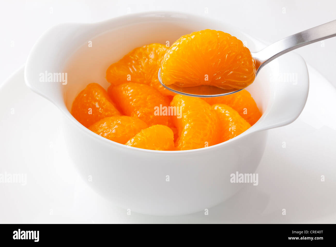 Mandarin oranges from a can, one segment being lifted with a spoon. - Stock Image