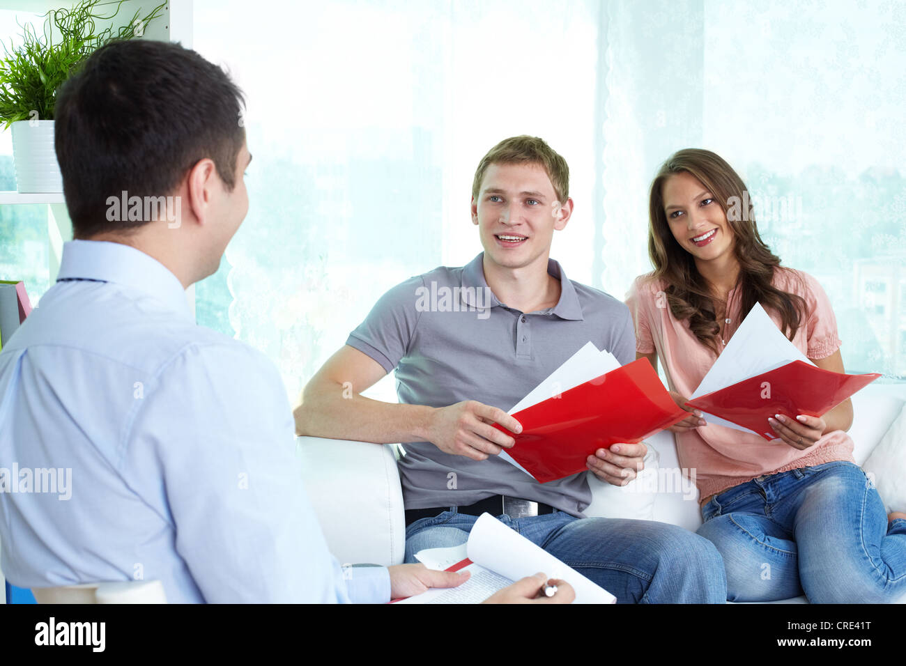 Confident insurance agent settling the matters with a young cheerful couple - Stock Image