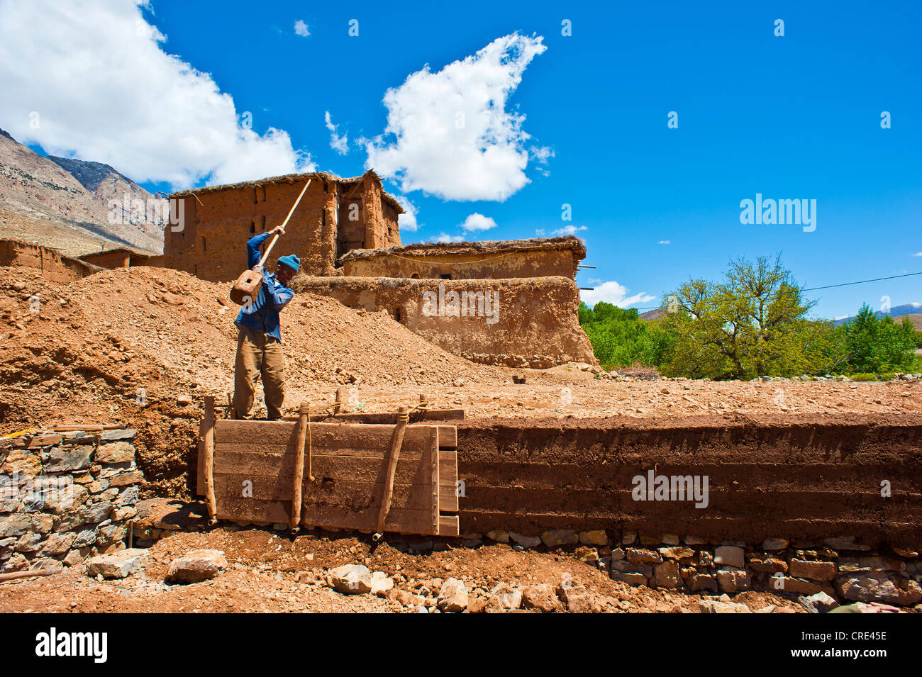 Worker building a rammed-earth wall for a new house, the clay is compacted in a mould box with a wooden pestle, - Stock Image