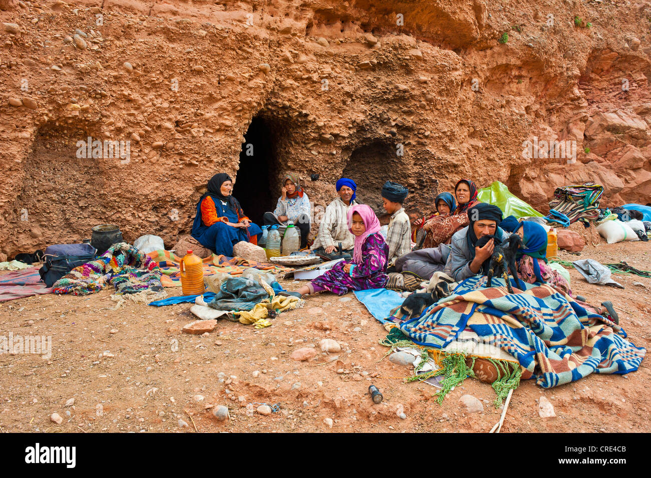 Nomadic cave-dwellers, Berbers, a family with several children sitting in front of their cave-dwelling, Dades Valley - Stock Image