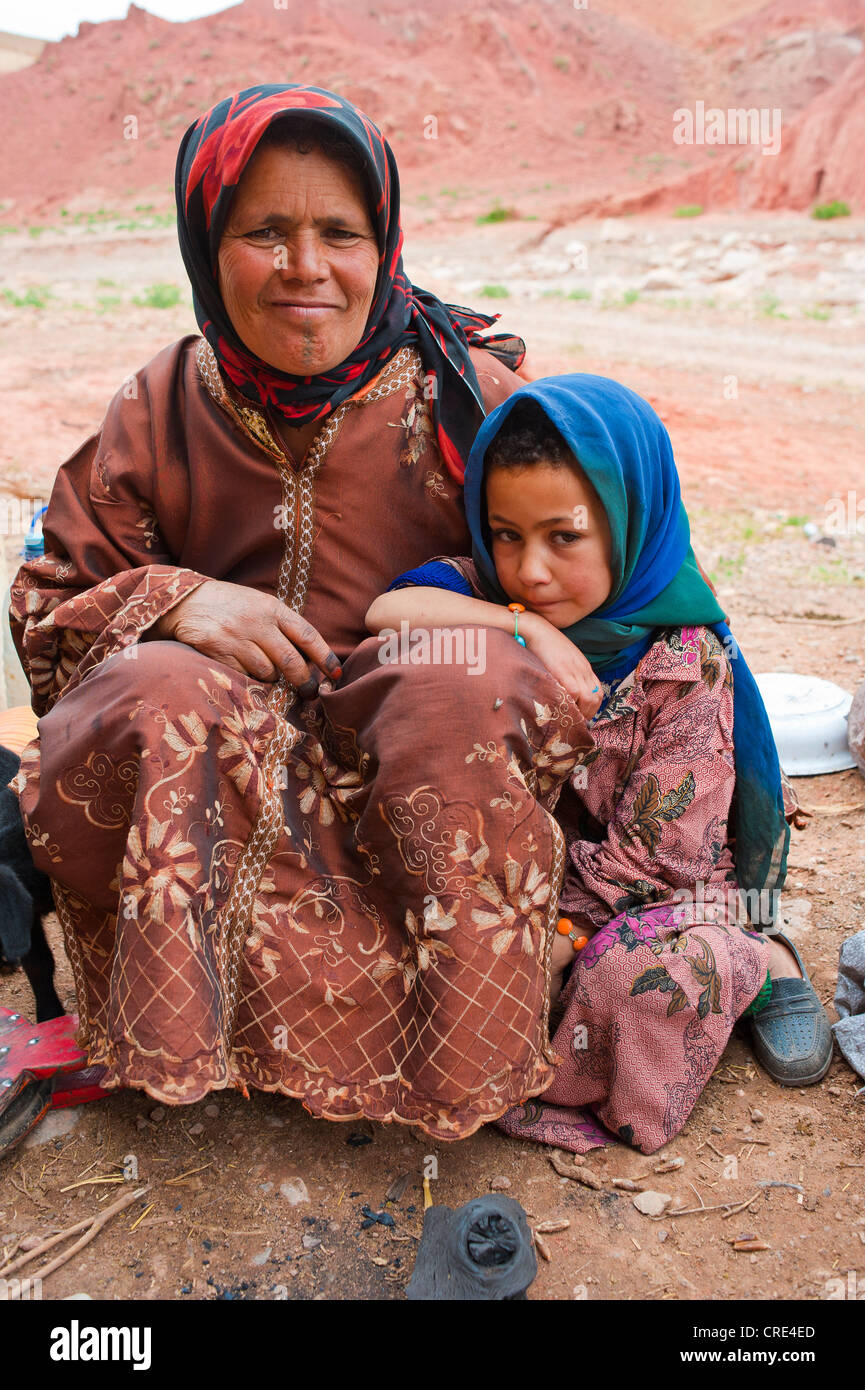 Nomadic cave-dwellers, Berber, a friendly woman and a little girl sitting on the floor, Dades Valley, High Atlas - Stock Image