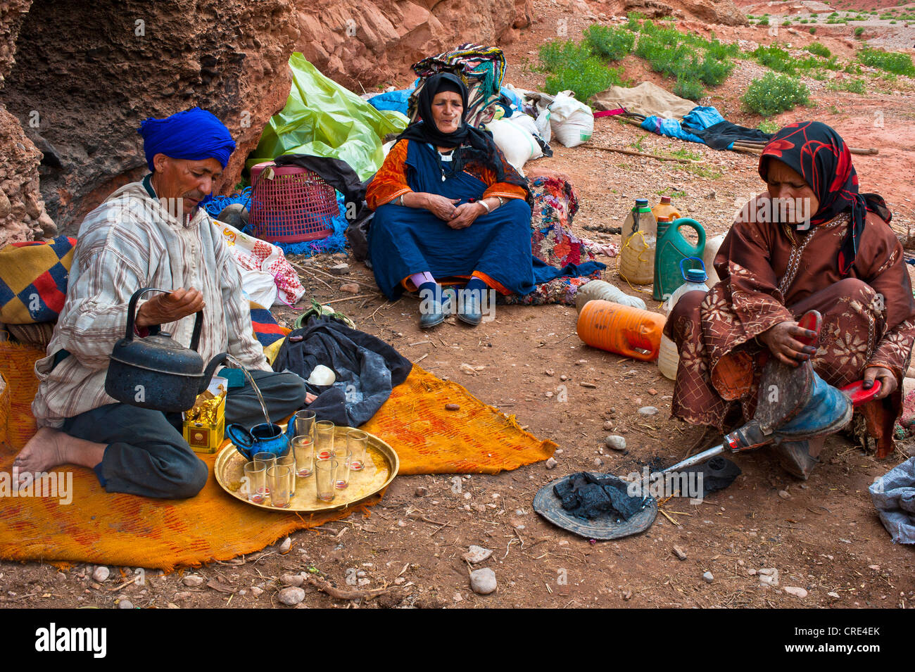 Nomadic cave-dwellers, Berber, a man wearing a blue turban is pouring a cup of tea, a woman is using bellows to - Stock Image